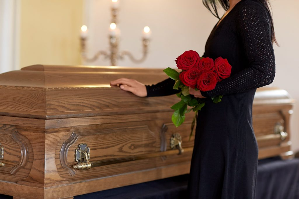 woman holding a red rose in a funeral